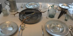 assortiment d'assiettes et couverts en étain sur une table