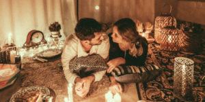 couple amoureux couché au sol entouré de bougies