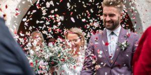couple de mariés qui sort de l'église - lancer de pétales et confettis
