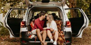 couple faisant un pique-nique dans le coffre de la voiture au milieux d'un bois