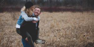 couple dans la nature homme qui porte femme sur son dos