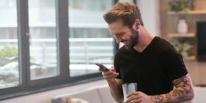 homme sourit en recevant un SMS sur son GSM idée anniversaire couple