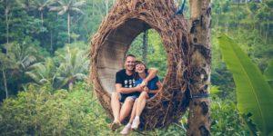 expérience insolite, couple qui s'enlace et rit dans un grand nid dans les arbres au milieu des palmiers anniversaire de couple que faire