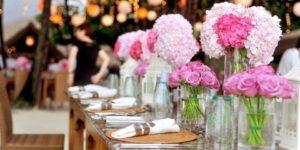 table de fête réception de mariage avec bouquets roses de roses et hortensias
