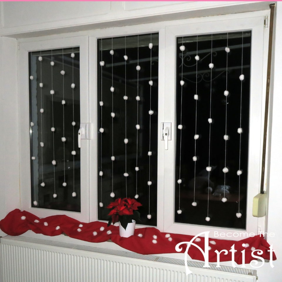 fenêtre décorée avec des guirlandes de boules d'ouate